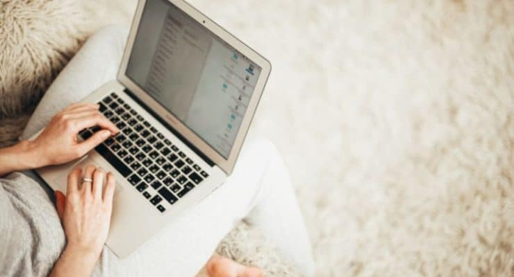 Woman on laptop sitting on fluffy rug - post regarding how to find freelance writing jobs online