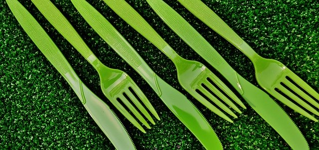 Green plastic cutlery on green grass