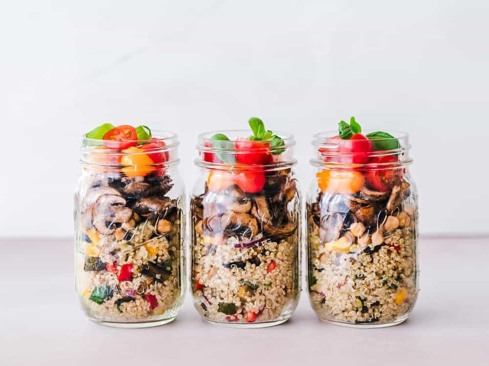 Home meal prep: three salad mason jars with layers of cous cous, mushrooms, and fresh tomatoes and basil.