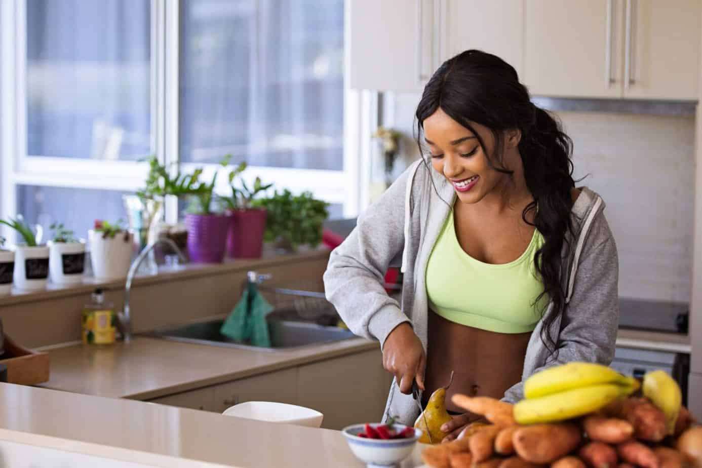 Get fit at home: smiling woman in a sports bra and grey tracksuit jacket cutting a pear in her kitchen with fresh fruit and vegetables in the foreground.