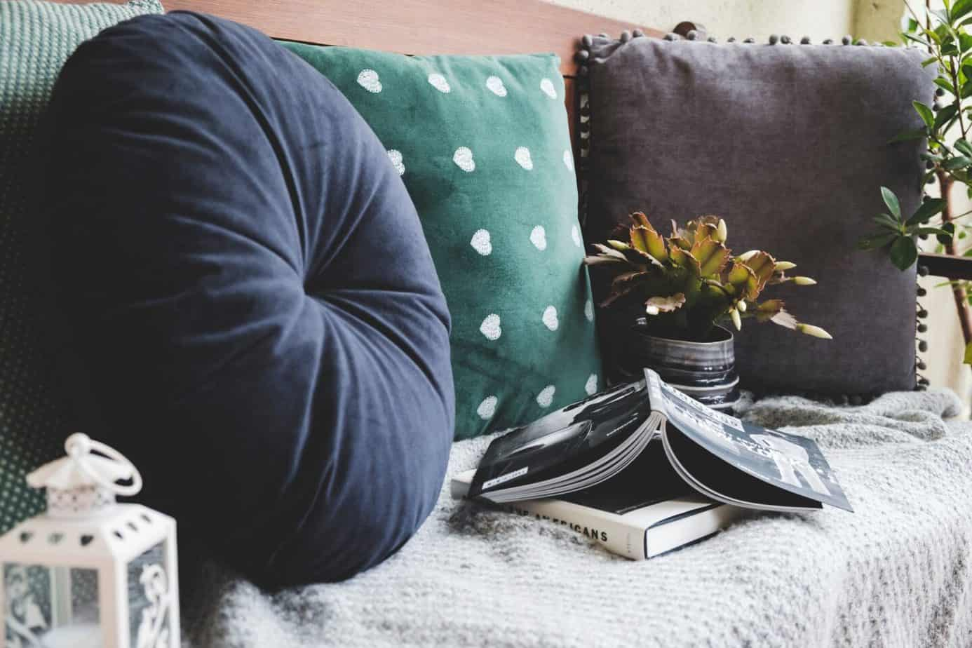 Three cushions, some books, and a house plant for budget ways to do up your living room.