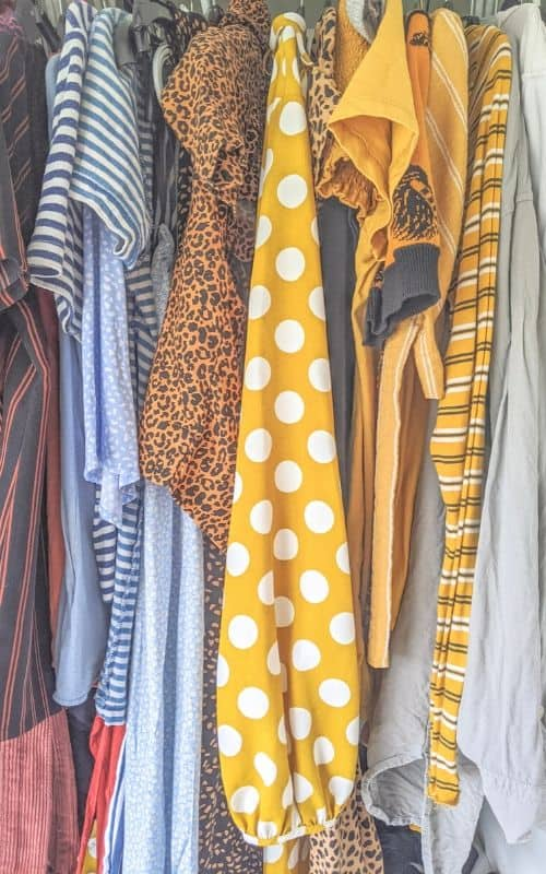 Sell clothes online: colourful clothes hanging next to one another. A yellow sleeve with white polka dots dominates the middle of the photo.