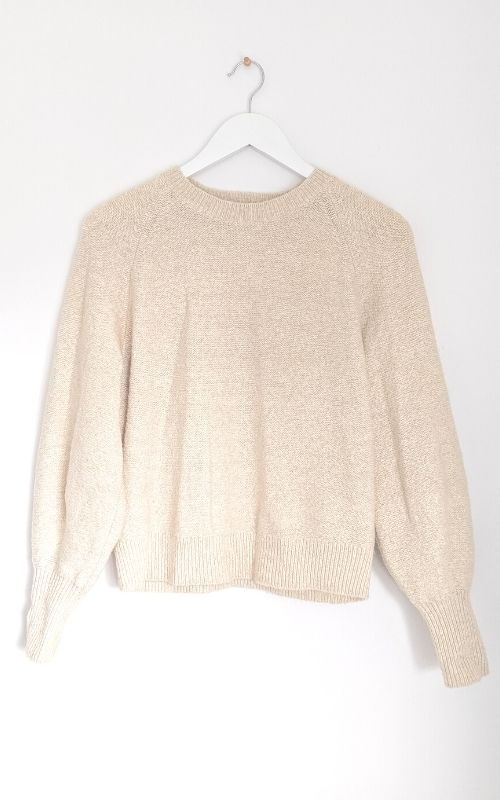 Sell clothes online with good photos: cream jumper on a white hanger against a white wall in natural light.
