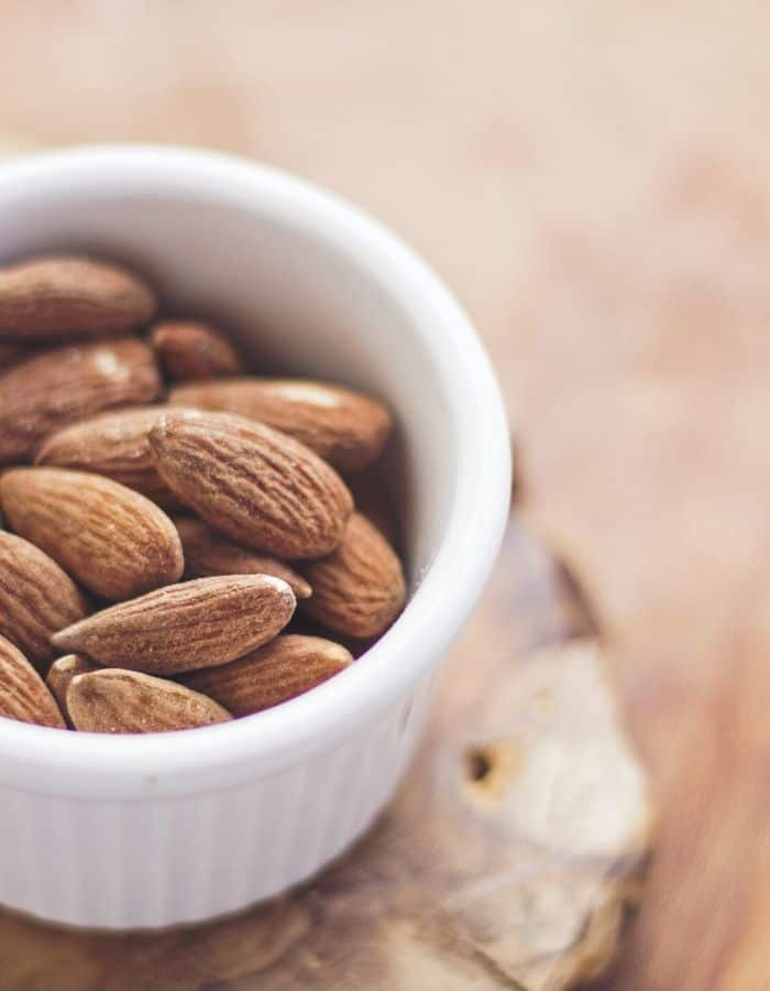 small white bowl with whole almonds